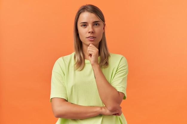 Pensive jolie jeune femme en t-shirt jaune garde les mains jointes en pensant et en regardant l'avant isolé sur un mur orange