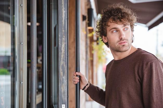Pensive mélancolique beau jeune homme bouclé en sweetshirt marron regardant loin et entrant