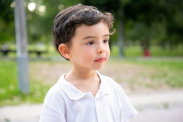 Pensive mignon garçon aux cheveux noirs debout dans le parc d'été et à la recherche de suite. photo en gros plan. concept de l'enfance