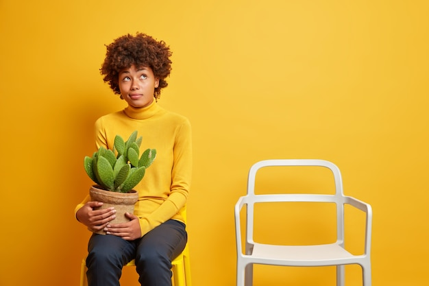 Pensive pensive jeune femme à la peau sombre porte pot de cactus regarde ci-dessus pense à quelque chose porte col roulé décontracté