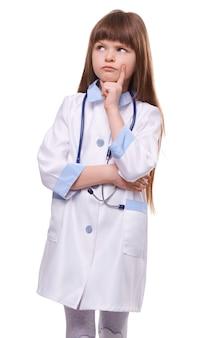 Pensive petite fille médecin en blouse médicale blanche et stéthoscope sur fond blanc isolé
