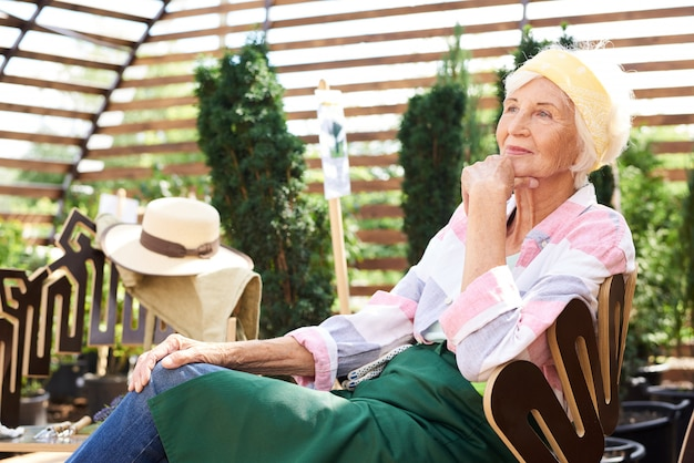 Pensive senior woman resting in garden