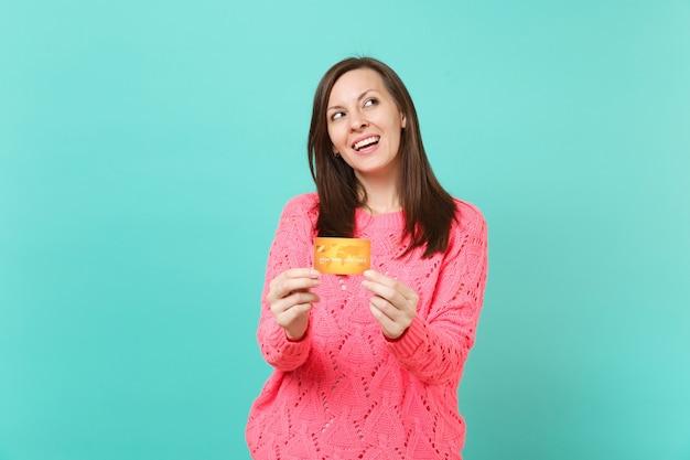 Pensive superbe jeune fille en pull rose tricoté en levant, tenant dans les mains une carte de crédit isolée sur fond de mur bleu turquoise, portrait en studio. concept de mode de vie des gens. maquette de l'espace de copie.