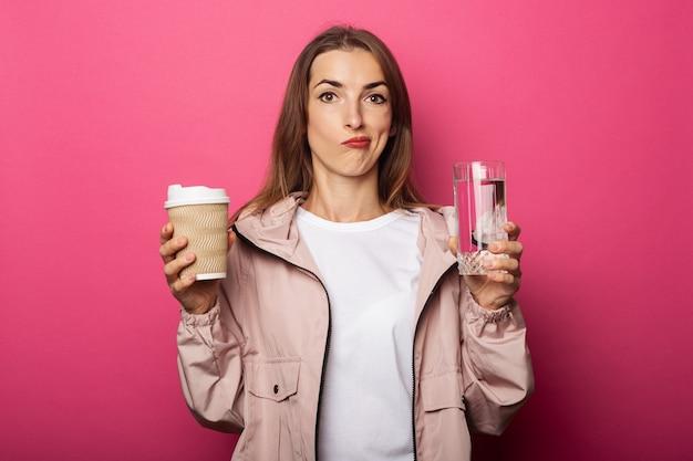 Pensive young woman holding tasse de papier et tasse en verre avec de l'eau sur la surface rose