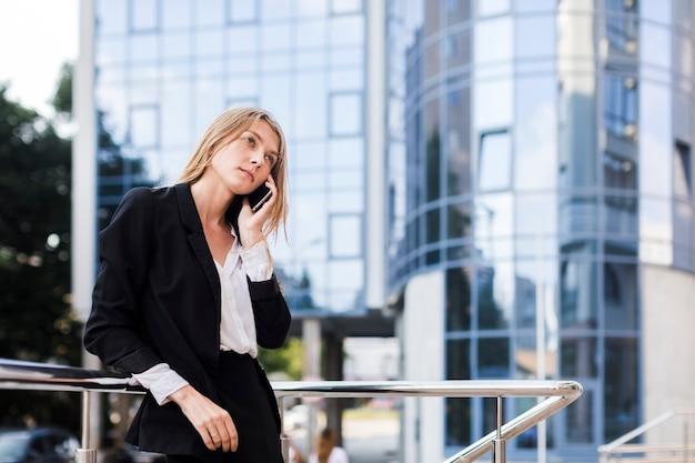 Pensivement femme parlant au téléphone