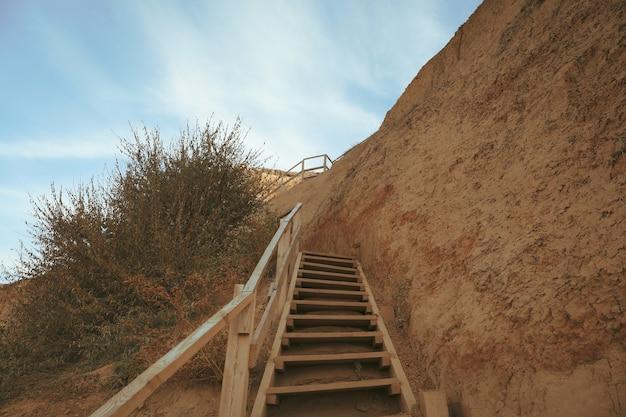 Pente d'argile avec marches en bois contre le ciel bleu