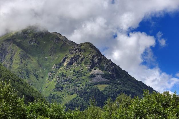 La pente d'une montagne avec de la végétation est cachée par un nuage. changement de temps dans la région montagneuse des montagnes du caucase.