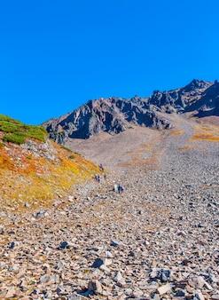 Pente en pierre du volcan avec des touristes à pied.