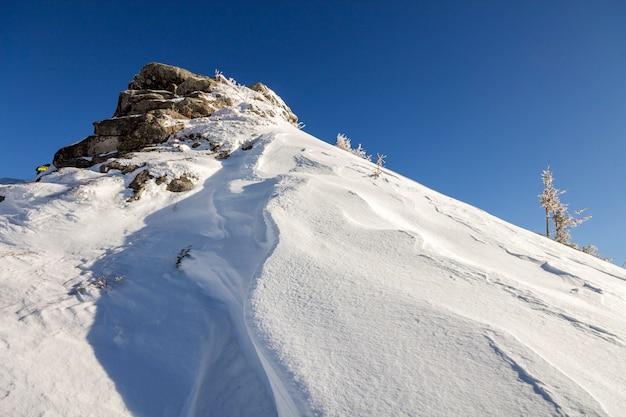 Pente raide de la colline de montagne avec de la neige profonde et blanche, un panorama lointain de la chaîne de montagnes ligneuses s'étendant jusqu'à l'horizon et des rayons de soleil brillants
