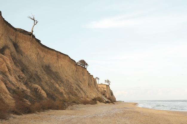 Pentes d'argile sur la plage de sable contre le ciel bleu