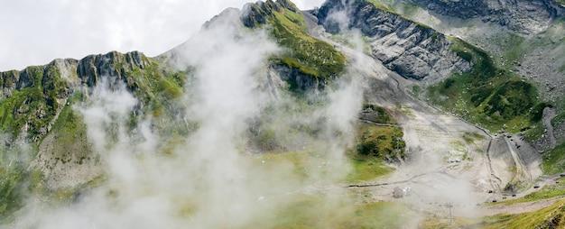 Pentes de montagne avec végétation et ciel nuageux