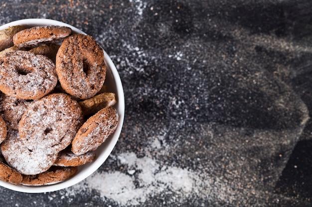 Pépites de chocolat fraîches cuites au four et biscuits frais d'avoine avec du tas de poudre de sucre dans un bol blanc fond noir