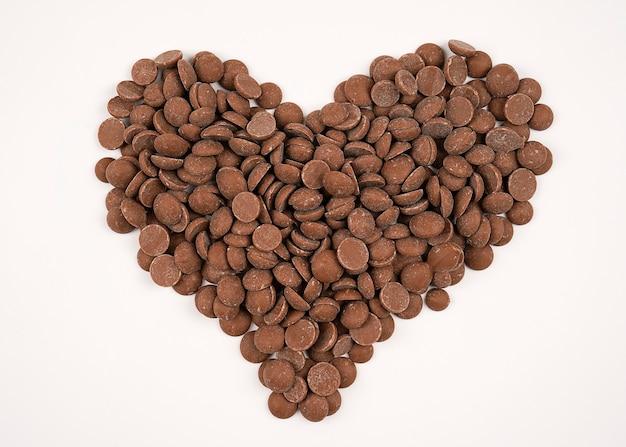 Pépites de chocolat noir placé sur blanc en forme de coeur, vue de dessus gouttes de chocolat