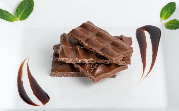 Pépites de chocolat sur une plaque blanche décorée de feuilles de menthe