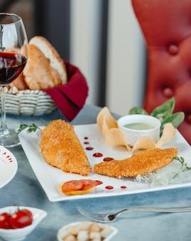 Pépites pépites de poisson servies avec une sauce spéciale et des frites