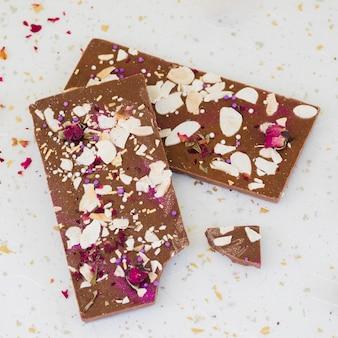 Pépites et pétales de rose sur tablette de chocolat