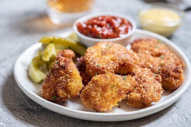 Pépites de poulet croustillantes frites maison avec ketchup et cornichons
