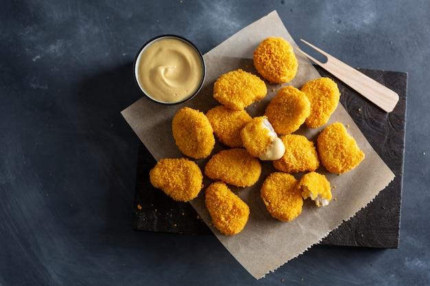 Pépites de poulet croustillantes savoureuses servies sur planche de bois avec de la moutarde sur une surface sombre.