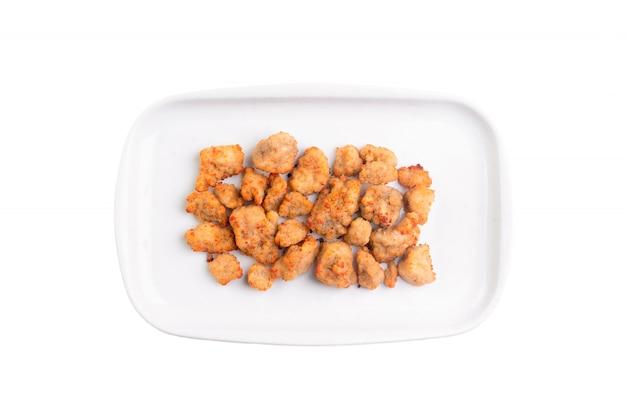 Pépites de poulet frit sur plaque blanche isolée.