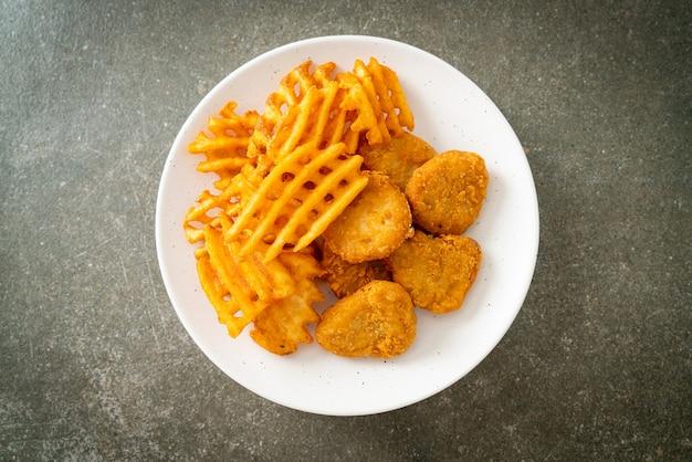 Pépites de poulet frit avec pommes de terre frites sur plaque