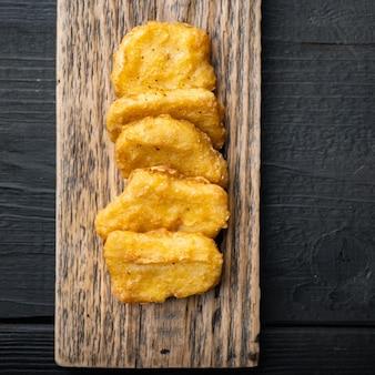 Pépites de poulet maison frites sur fond de bois noir, à plat, avec un espace pour le texte.
