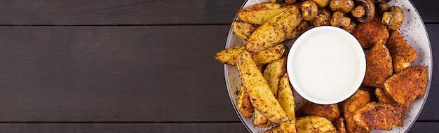 Pépites de poulet de restauration rapide avec du ketchup, des frites, des champignons au four. vue de dessus