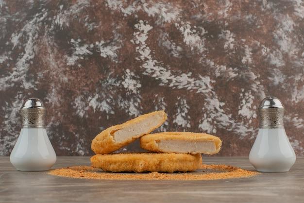 Pépites de poulet avec sel, poivre, miettes.