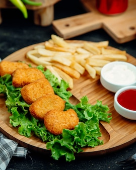 Pépites de poulet servies avec frites, ketchup et mayonnaise