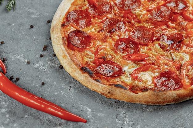 Le pepperoni tranché finement est une garniture de pizza populaire dans les pizzerias à l'américaine