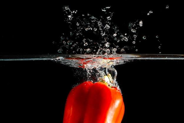 Pepperthrown de piment rouge dans l'eau. fond noir pour voir la fraîcheur et lumineux