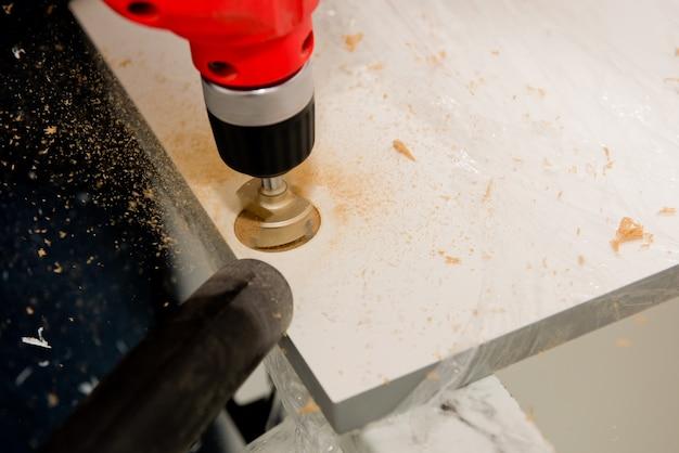 Perçage d'un trou pour une charnière sur une porte de meuble. mise au point sélective. fermer.