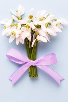 Perce-neige de fleurs fraîches sur fond bleu avec place pour le texte. carte de voeux de printemps. fête des mères. mise à plat.