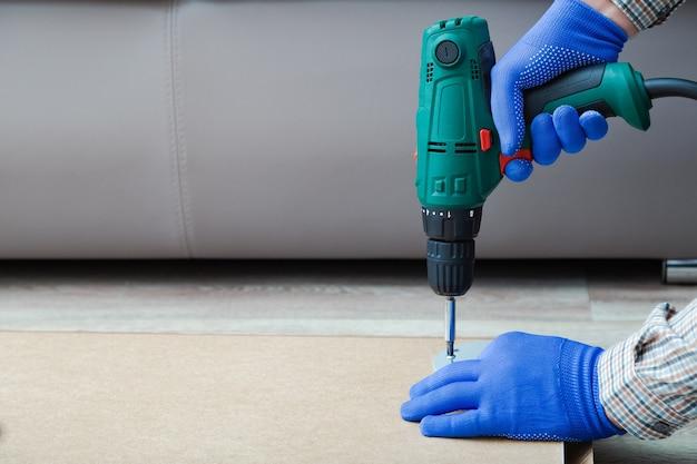 La perceuse électrique fonctionne entre les mains d'un bricoleur. mains masculines dans des gants à l'aide d'un outil de forage électrique pour assembler et réparer des meubles à la maison. espace de copie.