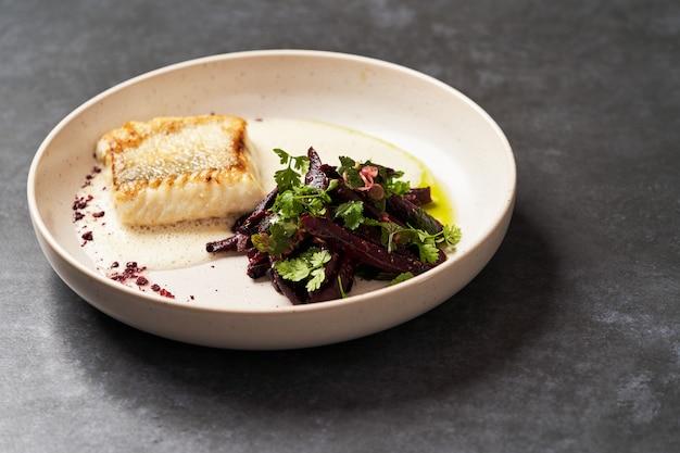 Perche de poisson frit avec des légumes sur un tableau blanc sur tableau gris