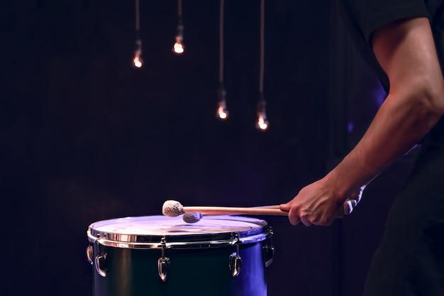 Le percussionniste joue avec des bâtons sur le tom au sol dans une pièce sombre avec un bel éclairage. concept de concert et de performance.