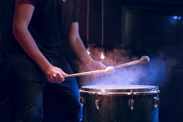 Le percussionniste joue avec des bâtons sur le tom au sol sous l'éclairage du studio. concept de concert et de performance.