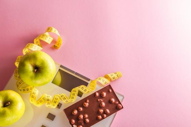 Perdre du poids avec des échelles, du ruban à mesurer, des pommes vertes et une barre de chocolat sur fond rose