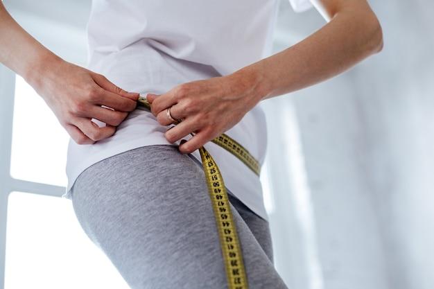 Perdre du poids. femme jeune chose mesurant sa taille et portant des vêtements à la maison