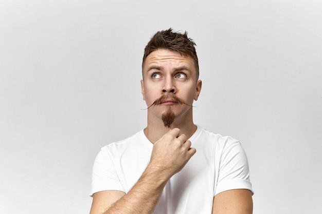 Perdu dans les pensées. vue de studio isolé attrayant élégant jeune hipster mâle européen avec barbiche et msutache en levant, ayant une expression faciale nerveuse impatiente, attendant quelque chose
