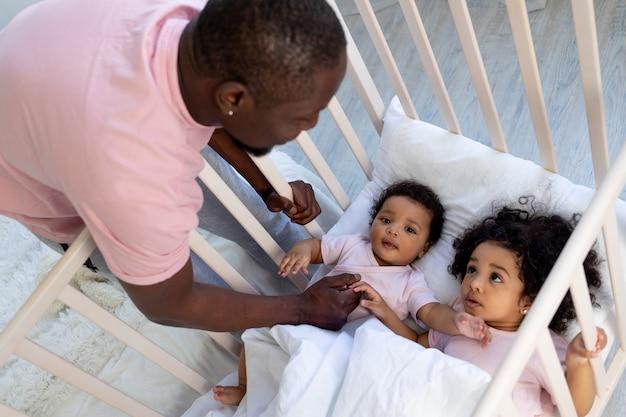 Un père afro-américain fait dormir les enfants dans le berceau, les enfants s'endorment ou se réveillent le matin