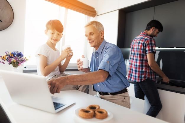 Un père âgé montre quelque chose sur un ordinateur portable à son fils.