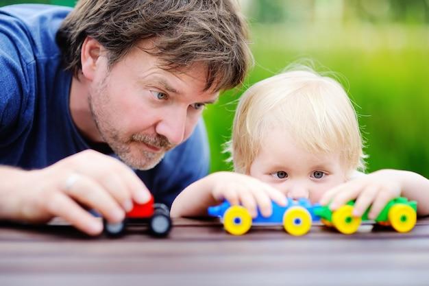 Père d'âge moyen avec son fils d'enfant en bas âge jouant avec des trains de jouet à l'extérieur.