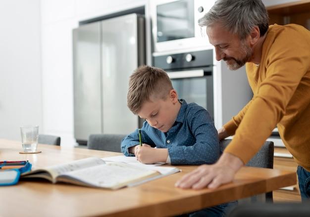 Père aidant l'enfant à faire ses devoirs
