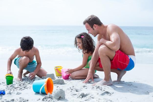 Père aidant des enfants à construire un château de sable sur la plage