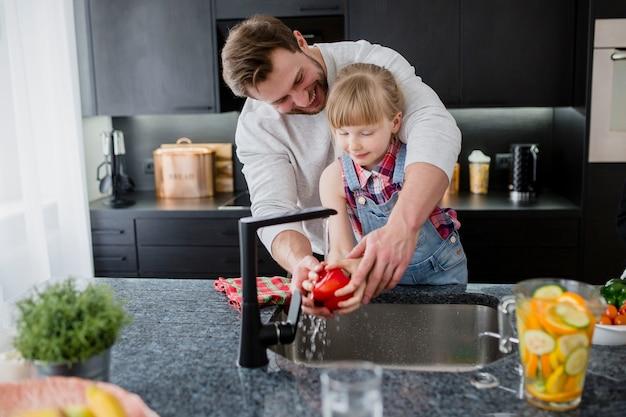 Père aidant une fille à laver le poivre