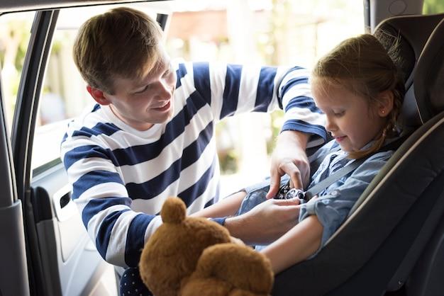 Père aidant à mettre sur la ceinture de sécurité