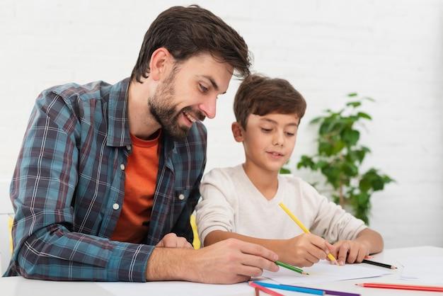 Père aidant petit fils à faire ses devoirs