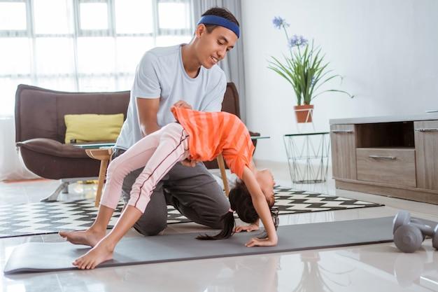 Père aidant sa fille à faire des étirements à la maison. enfant exerçant avec un parent faisant de la gymnastique