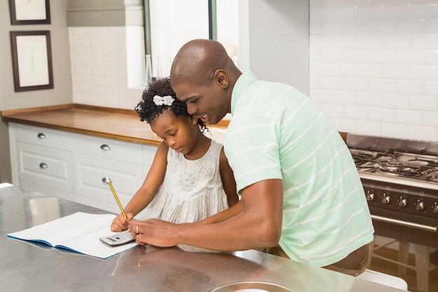 Père aidant sa fille à faire ses devoirs