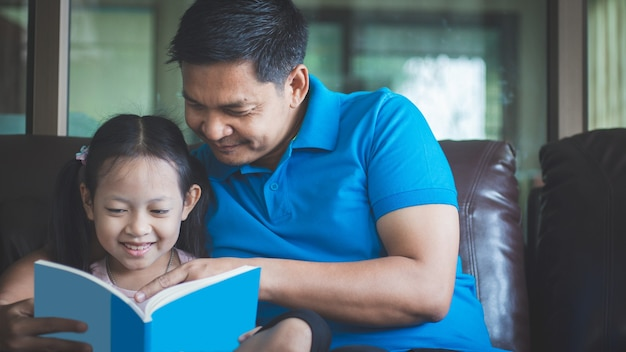 Père aidant sa fille à lire un livre et à faire ses devoirs avec le sourire et heureux à la maison. concept de fête des pères